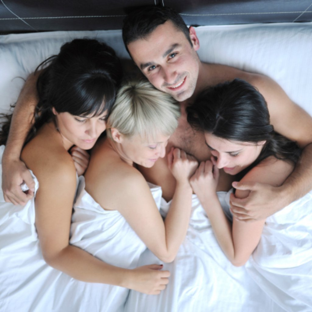 man 3 girls in bed