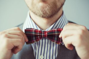 Close-up portrait of a man correcting bowtie