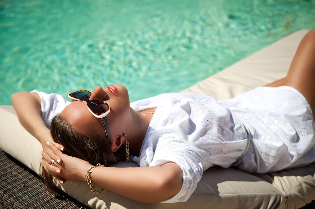 Beautiful woman holding hand behind head, lying on sun chaise-longue near luxury pool side. Young woman enjoying summer vacation.