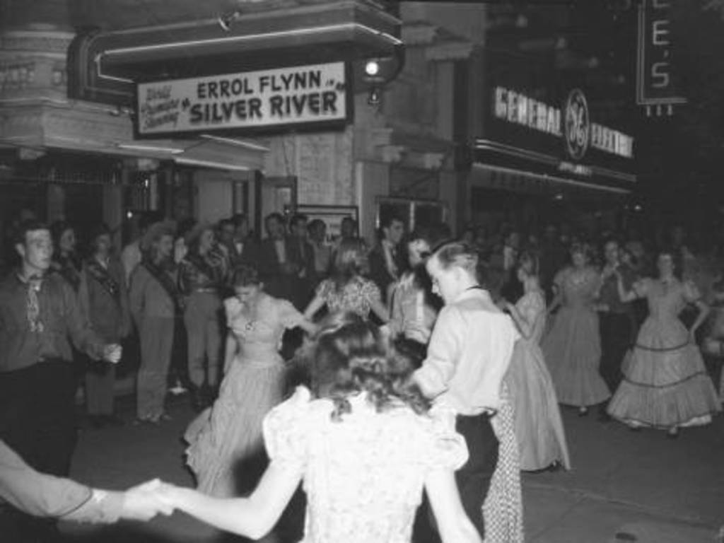 People perform a line dance in front of the Webber Theater at 119 South Broadway Street in Denver, Colorado. Photo from Denver Public Library's Digital Archive