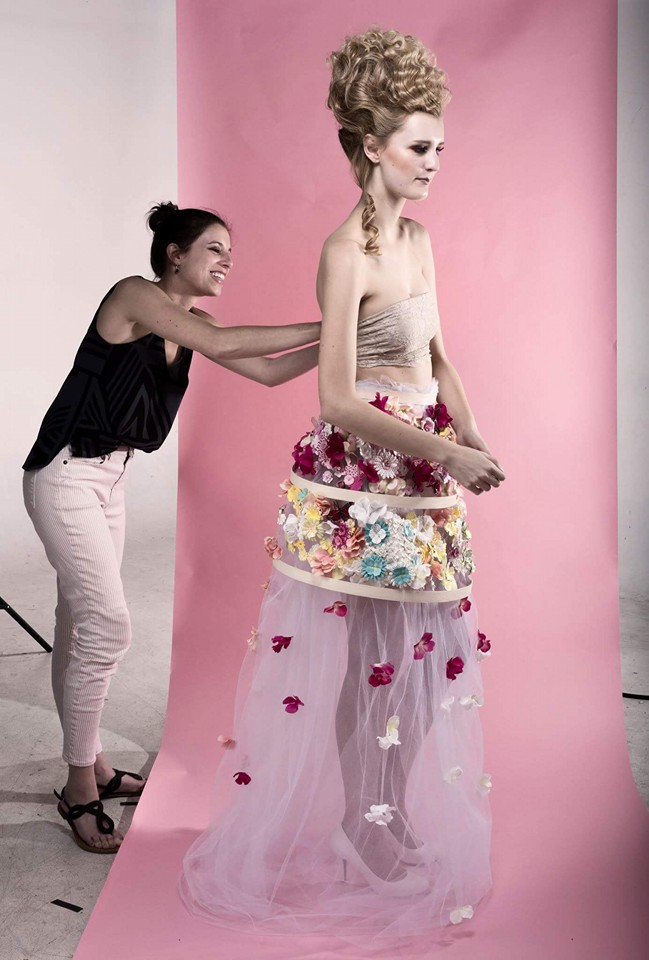 The designer, (left) preparing a model in her own designs for a photo shoot.