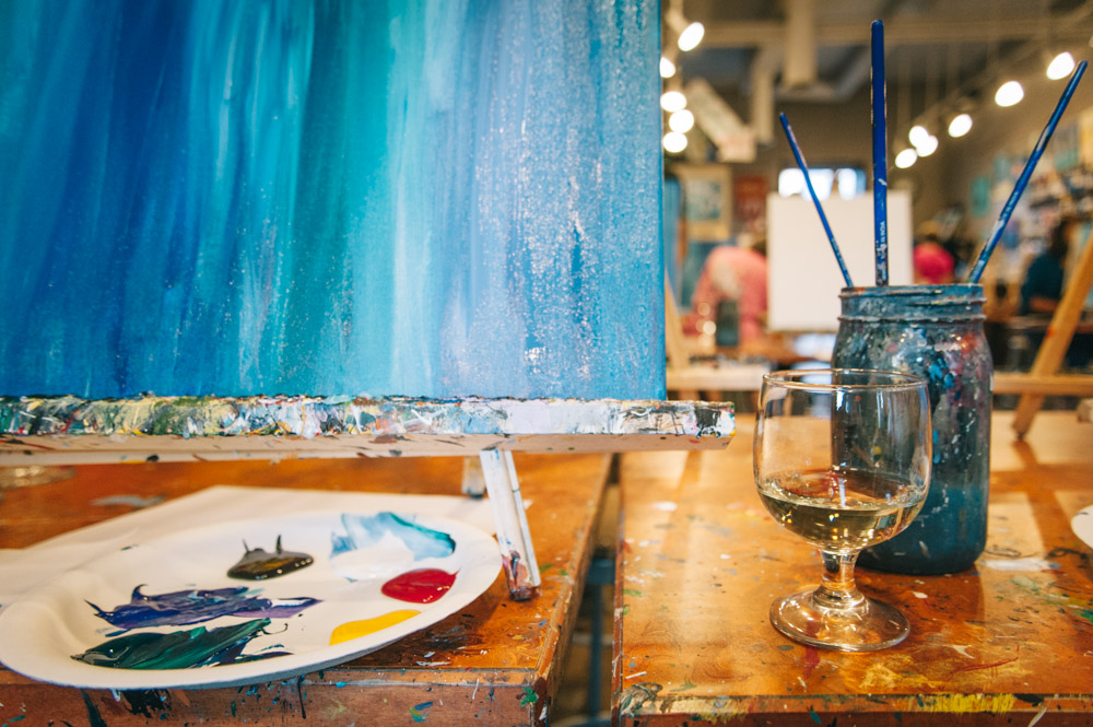 While the paint dries on the first layer, sip on a glass of wine.