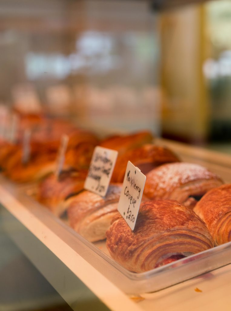 A display case filled with various croissant offerings.